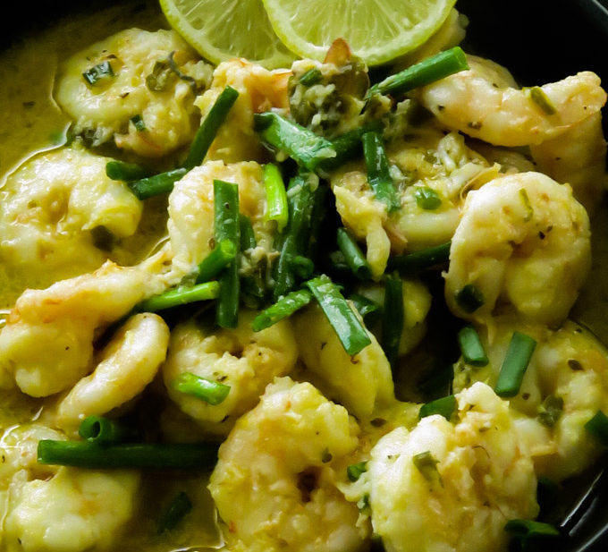 garlic butter shrimp in a bowl served with lime wedges