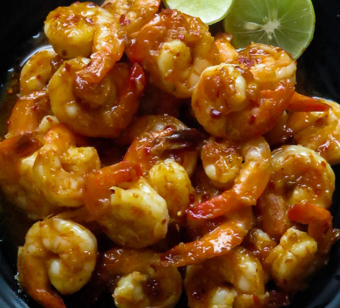 chilli garlic prawns in a platter with lime wedges
