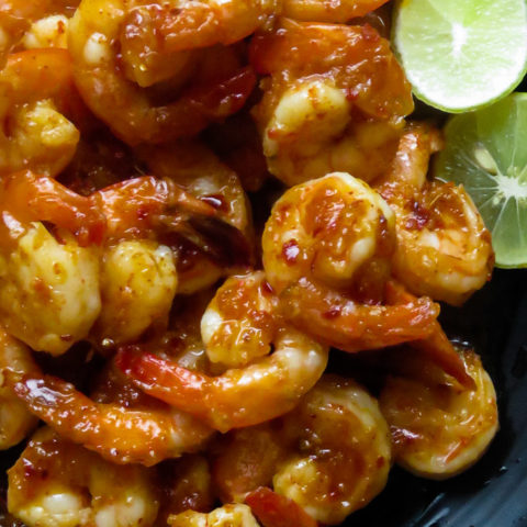 chilli garlic shrimp in a platter with lime wedges