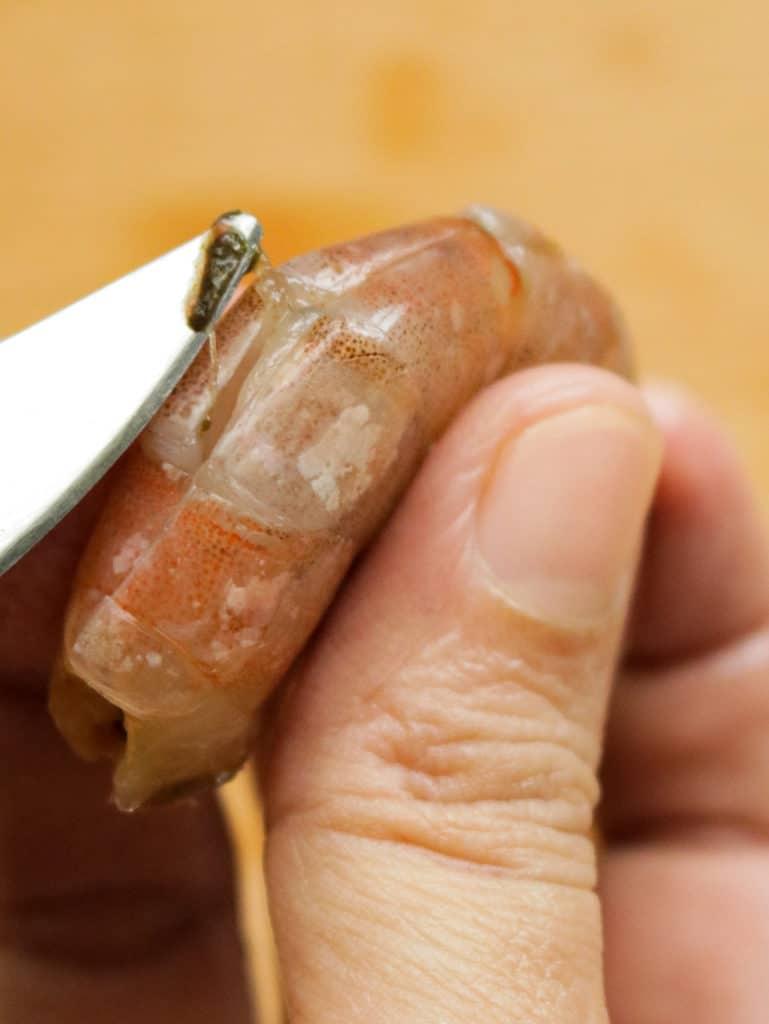 cutting the shrimp shell to remove the shrimp poo.