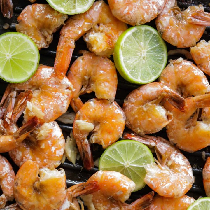 a tray of peel and eat shrimp with lime wedges