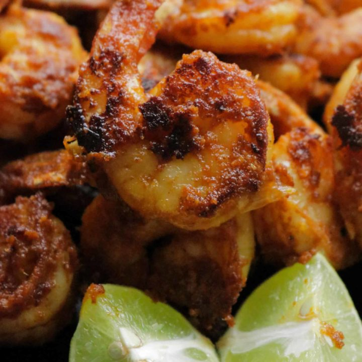 tandoori shrimp served with lime wedges.