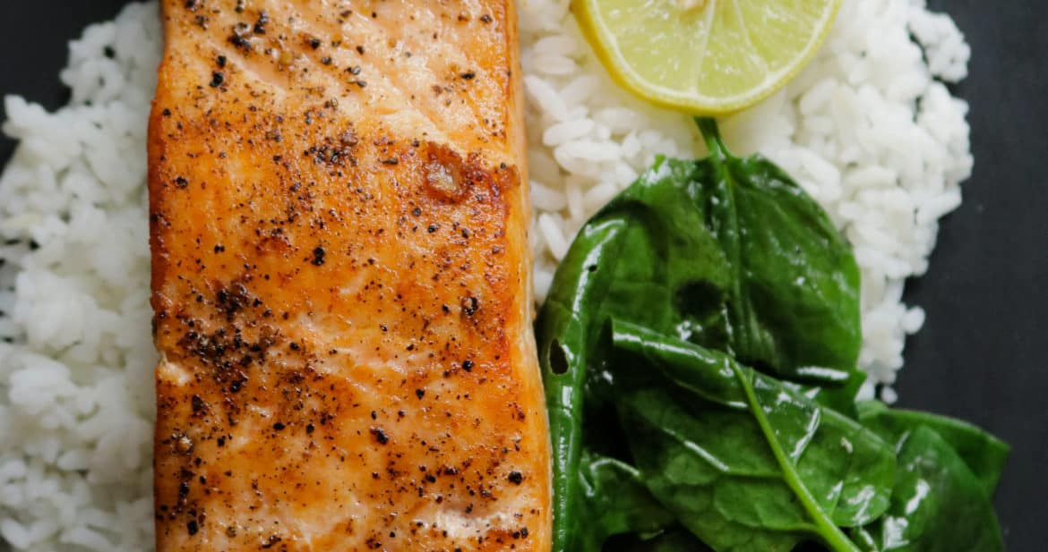 pan seared salmon serve with rice and spinach.